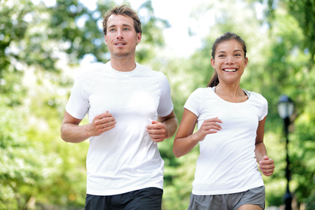 jog: Fitness healthy lifestyle. Happy couple running summer training for marathon in Central Park Manhattan, New York. Asian female model and Caucasian sport fitness male athlete enjoying jogging together. Stock Photo