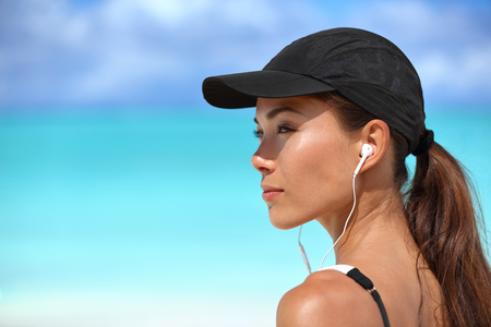 Fitness runner girl listening to smartphone music phone app on beach wearing earphones earbuds and running cap for sun protection. Asian woman healthy and active on summer vacation.