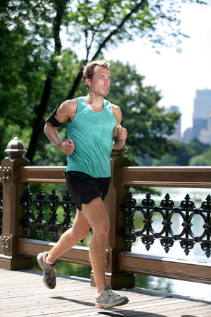 manhattans: New York City runner running listening to music with smartphone armband. Athletic young man exercising cardio using mobile phone app and earphones for workout in Manhattans Central Park in summer.