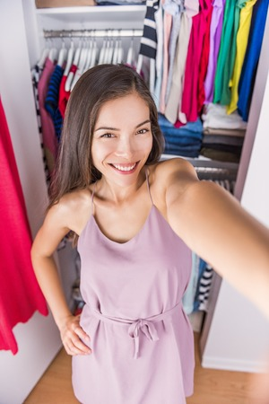 changing room: Changing room Asian woman taking selfie picture of her outfit. Young ethnic girl trying on a fashion dress taking a photo of herself in the fitting room or at home in her bedroom walk-in closet. Stock Photo