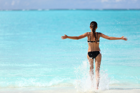 feeling happy: Freedom bikini woman running carefree with arms up swimming splashing water in ocean on tropical beach. Happy success girl from behind feeling free in summer Caribbean travel vacation.