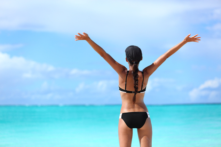 arms up: Happy freedom bikini woman on free tropical beach summer vacation. Joyful girl from behind with arms raised up in success swimming in ocean water sunbathing happily. Winning and carefree.