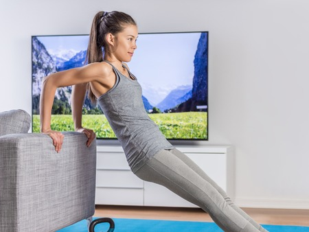 workouts: Home fitness woman strength training arms watching online tv dvd workouts doing bodyweight exercises in living room using sofa to do triceps exercise. Exercising Asian girl in her apartment indoors.