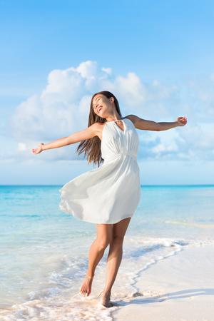 Vrijheid vrouw gevoel vrij dansen zorgeloos met open armen ontvangen in een elegante witte jurk aan het strand zonsondergang. Gezond leven Aziatisch meisje in de zomer vakantie. Succes, geluk, mindfulness concept.