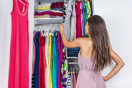 organized home: Home woman choosing her fashion outfit in dressing room. Woman in bedroom walk-in organized closet looking at clothes hanging deciding what shirt to wear in the morning. Shopping store clothing rack. Stock Photo
