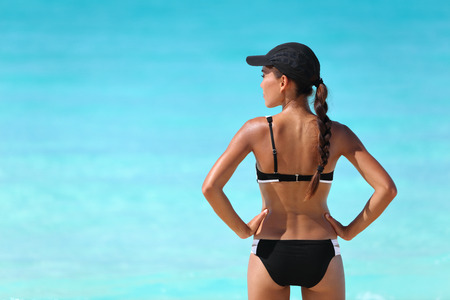Sexy sporty bikini woman looking over the ocean water for beach watersports. Active healthy Asian girl model standing from behind in swimwear and cap on sunny summer travel vacation. Stock Photo