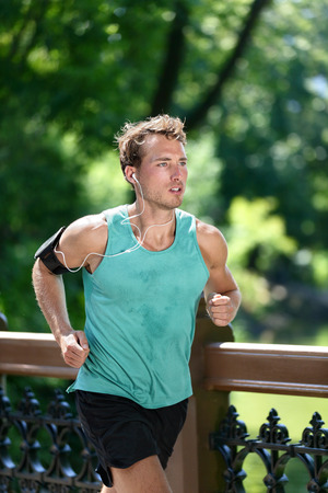Runner running listening to music with earbuds and fitness armband with workout app. Male athlete training during summer in urban New York city Central park sweating in sportswear activewear clothing. Banco de Imagens