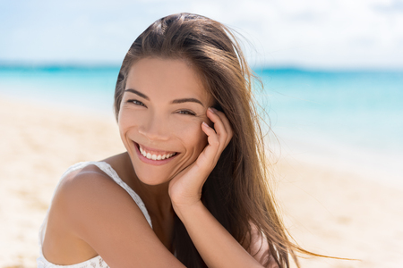 chinese adult: Healthy beautiful Asian multiracial woman on beach. Portrait of pretty Chinese Caucasian mixed race brunette girl in her 20s relaxing on summer vacations. Confident and modern young adult.