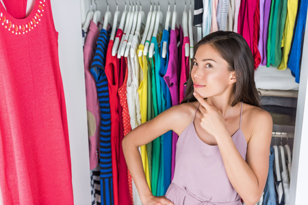 changing room: Home closet or store clothing rack changing room. Woman choosing her fashion outfit. Shopping girl thinking what to wear in front of many choices of dresses and clothes in organized clean walk-in.