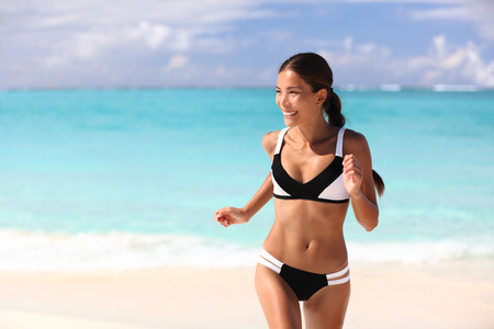 Happy bikini woman having fun on beach holiday on tropical summer travel vacation. Sexy cute Asian girl with slim suntan body running playful sunbathing in sunny Caribbean destination. Stock Photo