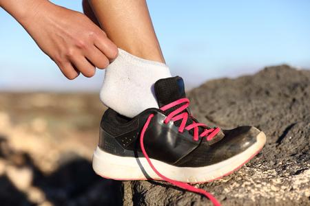 Agent die op fitness schoenen en loopschoenenclose-up buiten op bergachtergrond zet. Vrouwelijke atleet zich klaar voor marathonrace voorbereiding van haar voeten op trailrun.