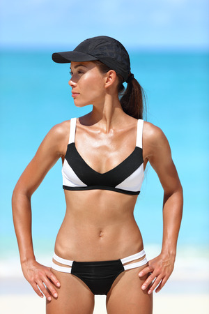 sun tanning: Sporty bikini fitness woman sun tanning sexy body on summer beach vacations. Active healthy Asian girl model standing in watersports swimwear against ocean background on sunny travel vacation. Stock Photo