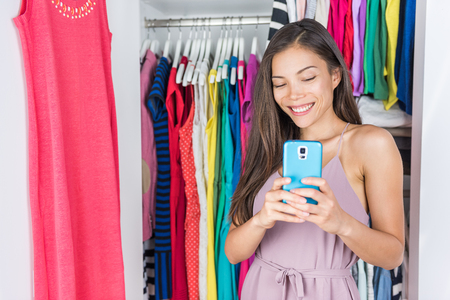 Shopping girl taking selfie in mirror of changing room at store or home walk-in closet in bedroom. Asian woman taking a photo of her outfit texting sms on social media using smartphone fashion app.