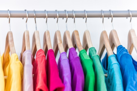 shirt hanger: Fashion clothes on clothing rack - bright colorful closet. Closeup of rainbow color choice of trendy female wear on hangers in store closet or spring cleaning concept. Summer home wardrobe. Stock Photo