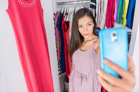 Smartphone selfie Asian woman in clothes closet of home bedroom or  store dressing room next to clothing rack. Shopping girl taking a photo of her outfit using smartphone fashion app. Social media.