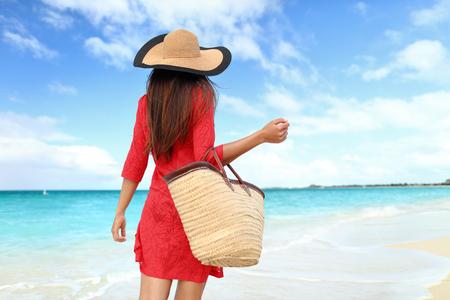 Toerist van de vrouw lopen op tropische de zomervakantie met zonnehoed, rode jurk en het strand zak ontspannen over reizen vakanties. Jonge dame van achter in luxe mode badmode.