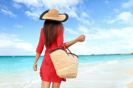 Woman tourist walking on tropical summer vacation wearing sun hat, red dress and beach bag relaxing on travel holidays. Young lady from behind in luxury fashion beachwear. Stock Photo