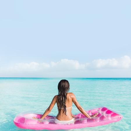 vacaciones de playa de relajación en la cama de agua del océano. Mujer de bikini de la parte posterior que se sienta en una piscina de color rosa colchón de aire que mira horizonte del mar turquesa perfecta virgen en destino tropical flotante.