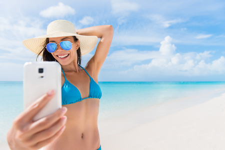 Summer beach vacation girl taking fun mobile selfie photo with smartphone. Cute Asian woman wearing blue sunglasses posing for phone self-portrait photo enjoying suntan in tropical travel holidays. 스톡 콘텐츠