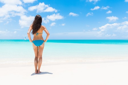 woman bathing: Bikini woman standing on white sand beach vacation getaway. Sexy fashion model with lean legs and toned body relaxing on luxury paradise sun destination on summer vacation. Caribbean holidays. Stock Photo