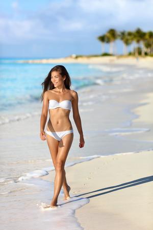 Sexy Asian Bikini Frau am Sonnenuntergang Strand Urlaub zu Fuß. Chinesisch kaukasischen Mädchen mit schlanken und getönten gebräunten Körper weiße Art und Weise der Badebekleidung tragen auf tropische Sommer-urlaub spazieren zu entspannen. Standard-Bild