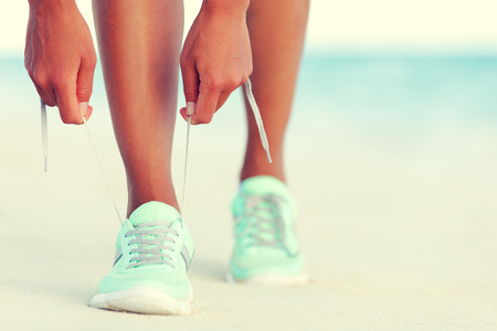 jogging: Healthy runner woman tying running shoes laces getting reay for beach jogging. Closeup of hands lacing cross training sneakers trainers for cardio workout. Female athlete living a fit and active life. Stock Photo