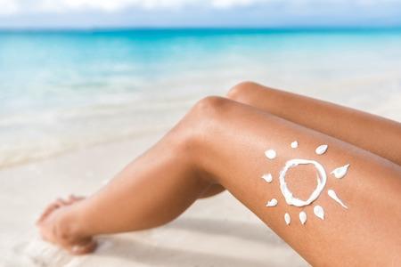 Sonnenschutz Sonne auf Sonnen Beine entspannen Gerben am tropischen Strand Urlaub Zeichnung Lotion. Frauen Unterkörper liegend mit Sunblocker-Creme in Form für Hautkrebs Sonnenbrand Pflegekonzept. Lizenzfreie Bilder