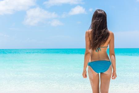 Bikini vrouw ontspannen staande op tropisch strand vakantie pronken slanke sexy kont. Mooi model van achter in blauwe zwembroek tegen turquoise water. Gewichtsverlies zomervakantie concept. Stockfoto