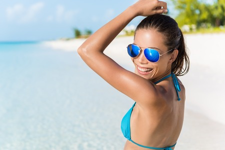 blissful: Sexy bikini beach woman having fun dancing in the sun relaxing laughing wearing blue fashion mirror sunglasses. Blissful young girl enjoying summer holiday travel on tropical vacation.