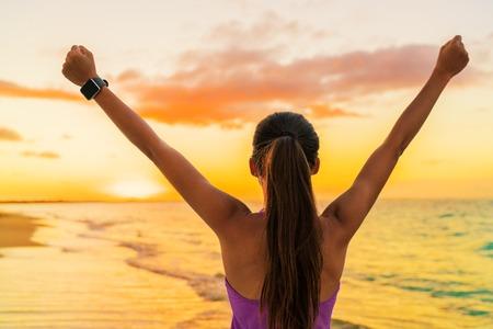 metas: Éxito de la mujer la libertad SmartWatch desde atrás al atardecer. Ganar aptitud atleta logro meta muchacha animando en la playa tropical verano que usa tecnología portátil reloj inteligente pulsera de la actividad.