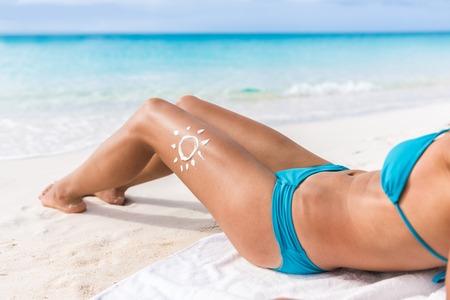 Sunscreen sun drawing lotion on suntan legs relaxing tanning on tropical beach holiday. Sexy bikini body woman sunbathing with sunblock cream in shape for skin cancer sunburn tan care concept.