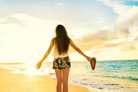 Vrijheid vrouw die zorgeloos dansen ontspannen op het strand in zonsondergang. Jongeren zomer lifestyle vakantie reizen. Vitaliteit gezond leven concept.