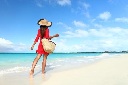 Beachwear vrouw toeristische met stro zonnehoed en het strand zak lopen op tropische de zomervakantie draagt sunhat en rode tuniekjurkje cover-up ontspannen op vakantiereizen van achteren. Stockfoto