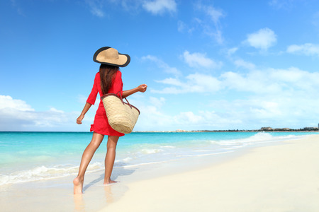 Beachwear woman tourist with straw sun hat and beach bag walking on tropical summer vacation wearing sunhat and red tunic dress cover-up relaxing on travel holidays from behind.