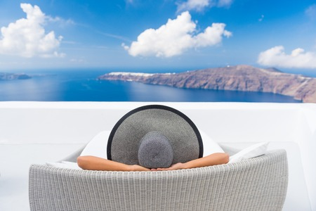 Travel vacation woman relaxing enjoying Santorini looking at famous view of Caldera. Young lady lying down on sun bed sofa lounge chair on holidays. Amazing view of sea. Europe travel destination. Stock Photo