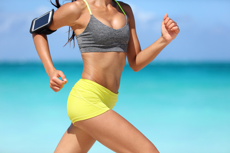 activewear: Running fitness woman runner wearing phone armband fast with speed. Hot girl midsection showing muscular legs and motion during intense cardio workout. Woman listening to music