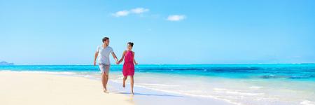 Panorama paio vacanze estive cammina sulla spiaggia. I giovani adulti divertirsi insieme godendo le loro vacanze viaggiano in perfetta fuga in destinazione tropicale soleggiato con incontaminate turchese acqua dell'oceano. Archivio Fotografico - 55657495