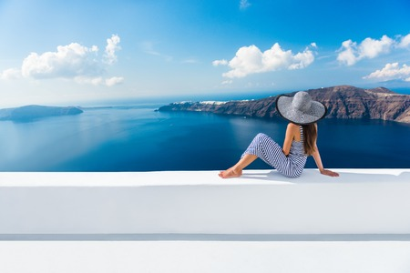Europe Greece Santorini travel vacation. Woman looking at view on famous travel destination. Elegant young lady living fancy jetset lifestyle wearing dress on holidays. Amazing view of sea and Caldera Standard-Bild
