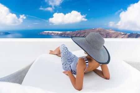 Vakantie reizen vrouw ontspannen genieten van Santorini kijken naar beroemde uitzicht op Caldera. Jonge dame liggend op zonnebank bank lounge stoel op feestdagen. Prachtig uitzicht op zee. reisbestemming Europa. Stockfoto