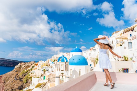 Europe tourist travel woman in Oia, Santorini, Greece. Happy young woman looking at famous blue dome church landmark destination. Beautiful girl in white dress on visiting the Greek island. Banque d'images