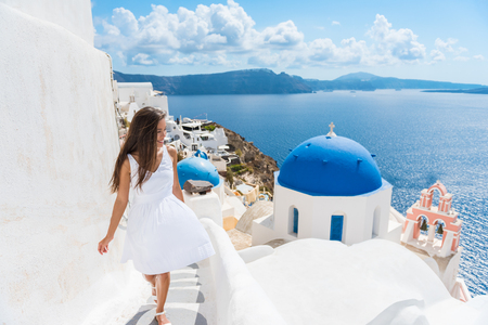 travler: Santorini travel tourist woman on vacation in Oia walking on stairs. Person in white dress visiting the famous white village with the mediterranean sea and blue domes. Europe summer destination