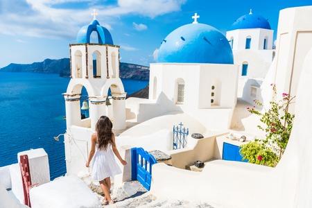 Santorin voyage femme touriste en vacances à Oia marcher sur les escaliers. Personne en robe blanche visiter le célèbre village blanc avec la mer Méditerranée et dômes bleus. destination estivale Europe.