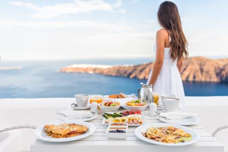 Ontbijttafel en luxe reizen vrouw op het eiland Santorini. Evenwichtig perfect ontbijt tafel geserveerd in het resort. Vrouwelijke toerist is op zoek naar mooi uitzicht op zee en de caldera genieten van haar vakantie. Stockfoto