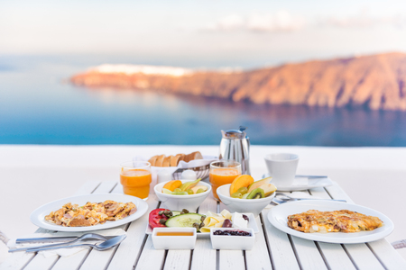 Breakfast table romantic by the sea. Perfect luxury breakfast table for two outdoors. Amazing caldera view on Santorini, Greece, Europe.