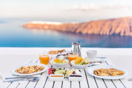 Ein Frühstückstisch romantisch am Meer. Perfekte Luxusfrühstückstisch für zwei im Freien. Erstaunlich Blick auf die Caldera auf Santorin, Griechenland, Europa. Standard-Bild