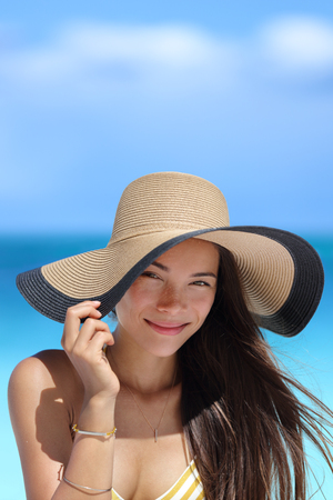 chinese adult: Portrait of Asian woman with beach hat smiling happy wearing fashion straw hat for skin care sun protection. Face skincare beauty. Beautiful Chinese Caucasian mixed race young adult girl on summer vacation travel. Stock Photo
