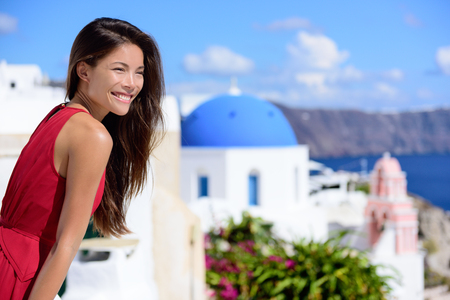 mediterranea: Santorini tourist Thira Greece island tourism - Asian woman wearing red dress on summer travel looking at view with the famous attraction three domes chapel church. Luxury destination.