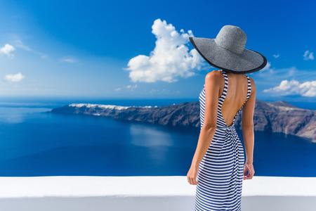 Luxe vakantie vrouw kijken naar weergave op Thera beroemde reisbestemming Europa. Elegante jonge dame leeft buitensporig jetset levensstijl draagt jurk op feestdagen. Prachtig uitzicht op zee en de Caldera. Stockfoto