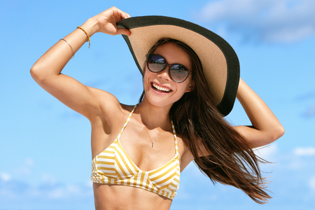 girl in a hat: Summer beach vacation woman enjoying the sun in bikini and sunglasses having fun happy with hair in wind holding on hat. Sexy Asian young adult on towel for tropical travel holidays concept.