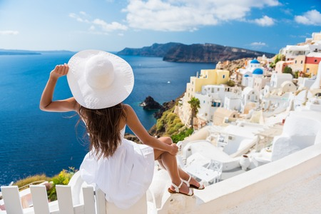 Tourist woman enjoying view of beautiful white village of Oia with Caldera and mediterranean sea. Young stylish female model wearing sunhat and red dress enjoying summer travel vacation in Europe.